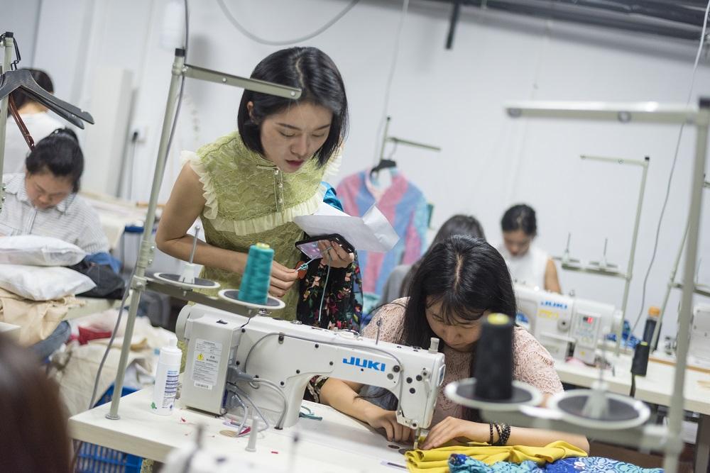 訂單急增,旗袍店工人們加緊趕製旗袍,常常加班到深夜。