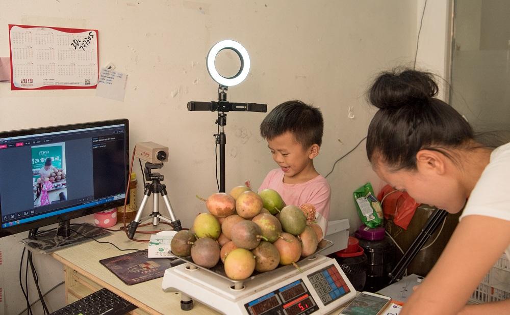 江西贛尋烏縣的百香果農戶潘秋霞,每日都會跟她的八歲兒子現身淘寶直播,向全國觀眾介紹、試吃、封箱再包裝當地特色的百香果。