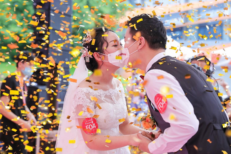 新郎與新娘隔著口罩親吻另一半,記下難忘一幕。